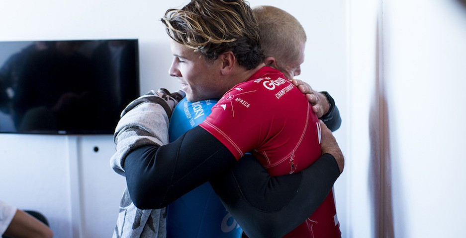 Julian Wilson hugs Mick Fanning (Blue) from the safety of shore after Fanning was attacked by a shark during the FInal of the JBay Open on Sunday July 19, 2015.